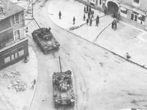 American Firefly tanks roll through a Normandy town